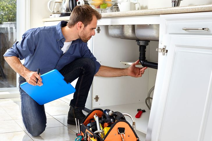plumber checking under a kitchen sink